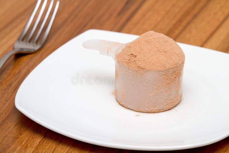 Schaufel des Schokoladenmolkeproteins auf einer Platte lizenzfreie stockbilder