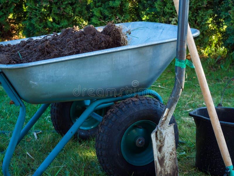 Schaufel, Schubkarre im Gartengras, mit Eimer, Gartenarbeitkonzept stockfotos