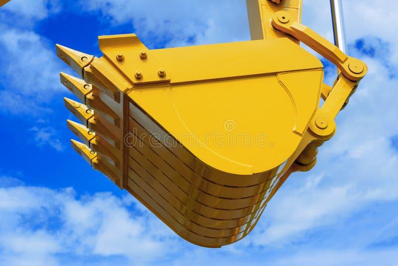 Schaufeleimer gegen den blauen Himmel, Aufzuglasten, Baumaschinen lizenzfreies stockbild