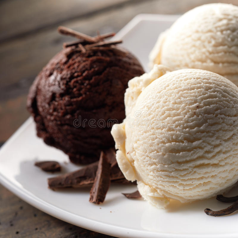 Schaufeln der Schokolade und des Vanilleeises auf Platte lizenzfreie stockbilder