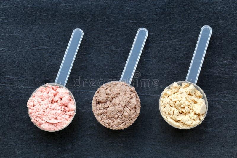 Schaufeln mit unterschiedlichem Aromaproteinpulver stockfotos