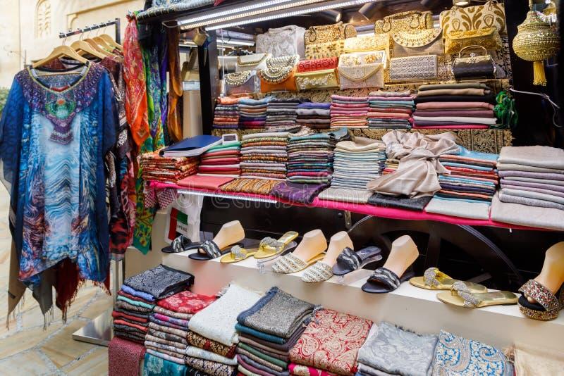 Schaukasten für einen Straßenhändlerstall mit den Schals, den Sandalen, den Kupplungen und der Kleidung der Frauen stockfotografie
