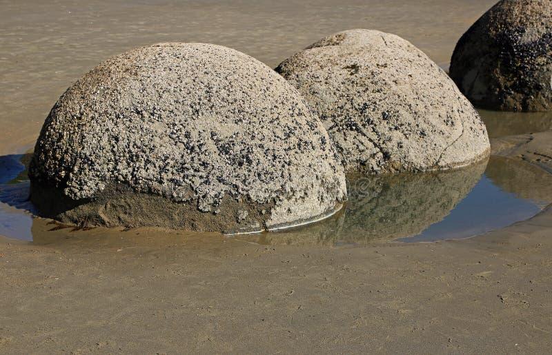 Schaukeln Sie Fluss-Steine im Wasser entlang Küste stockfotos