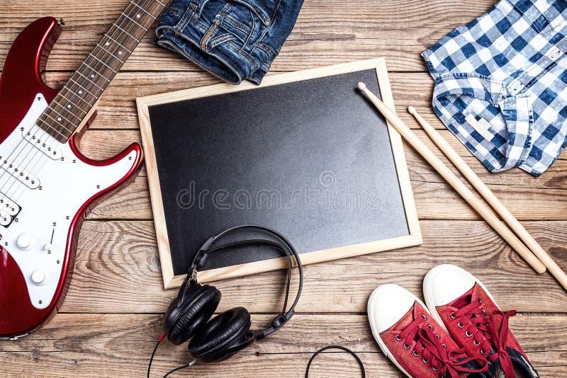 Schaukeln Sie Hintergrund mit Musikausrüstung, -kleidung und -Schuhen auf wo lizenzfreie stockfotos