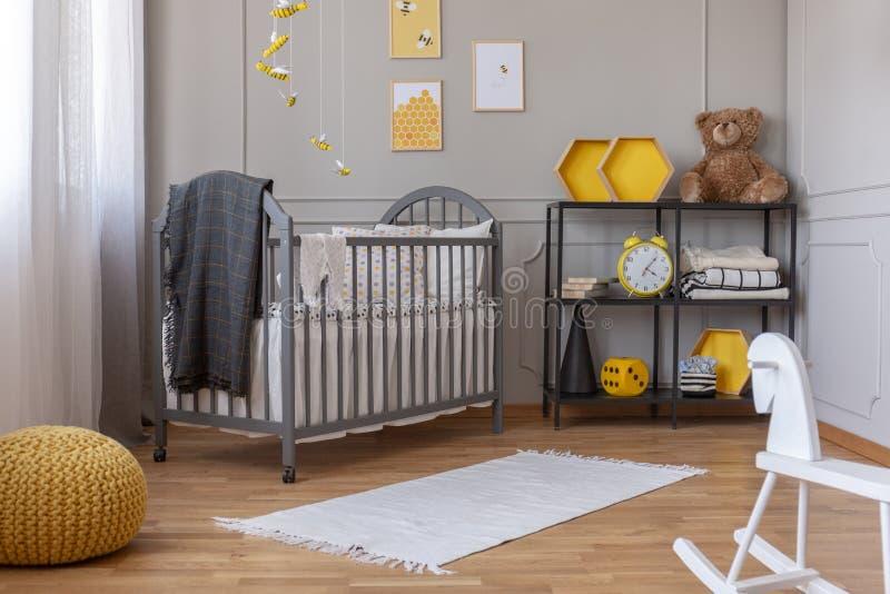Schaukelpferd und Wolldecke auf dem Boden des modischen Babyschlafzimmers stockbild
