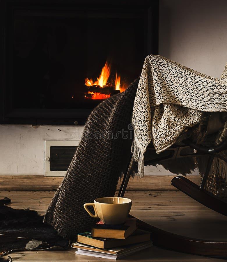 Schaukelstuhl mit Knitwolldecke, -büchern und -tasse Tee oder Kaffee vor Kamin stockbilder