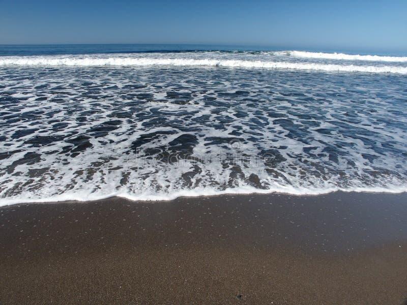Schaumgummi und Wellen von Meer stockfotografie