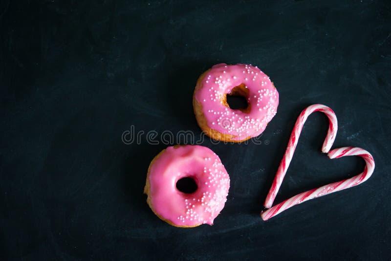 Schaumgummiring- und Zuckerstangeherz auf schwarzem Hintergrund stockfoto