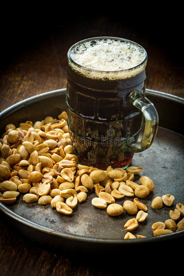 Schaumiges Bier-salzige Erdnüsse lizenzfreie stockfotografie