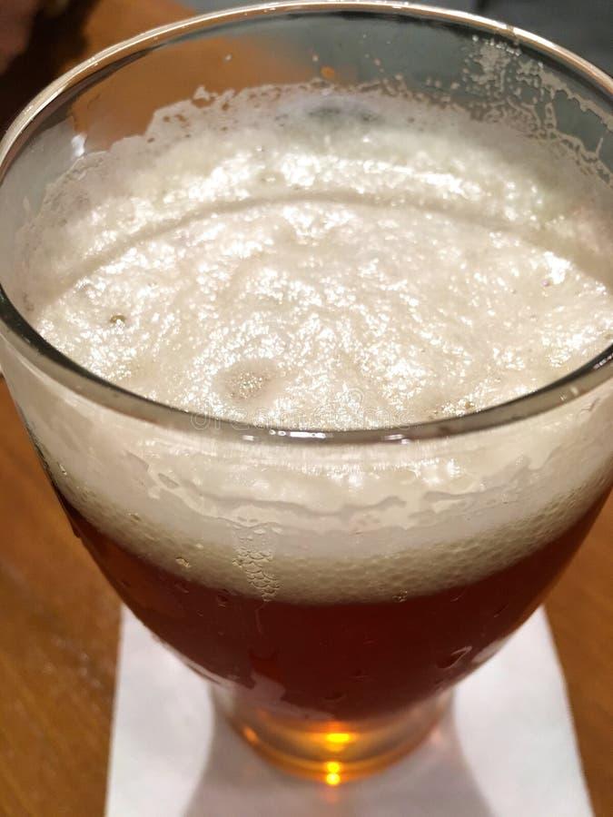 Schaumiges Glas Bier zeichnete unten schauen Verkürzung lizenzfreie stockbilder