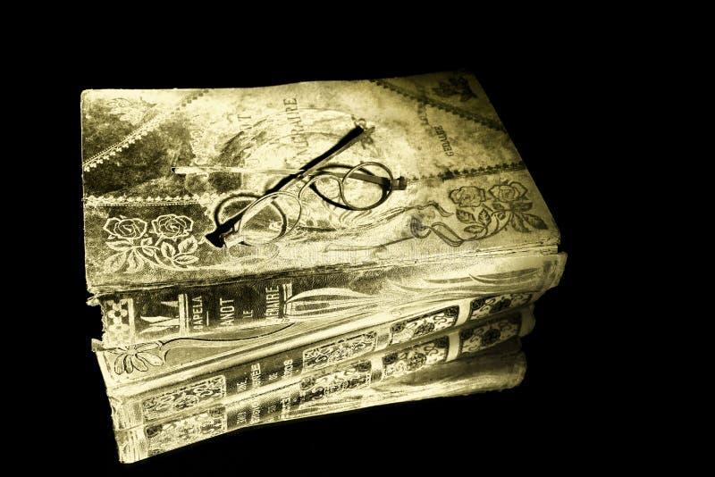 Schauspiel-Augengläser der Nahaufnahme alte auf dem Altgoldbuch, das auf Spiegel für Reflexion liegt lizenzfreie stockbilder