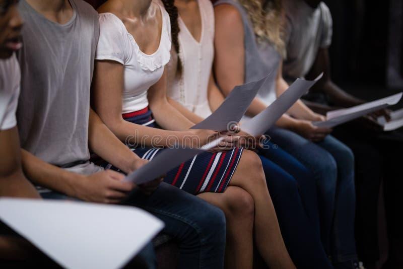Schauspieler, die ihre Skripte auf Stadium im Theater lesen stockbild