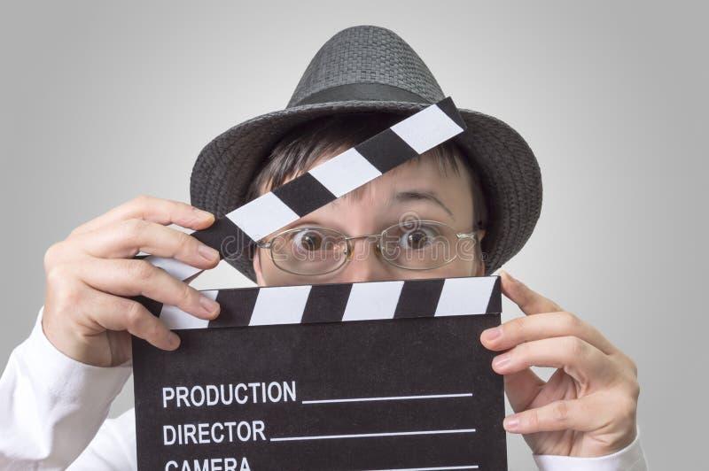 Schauspielerin mit Filmscharnierventil hinter Gesicht lizenzfreies stockbild