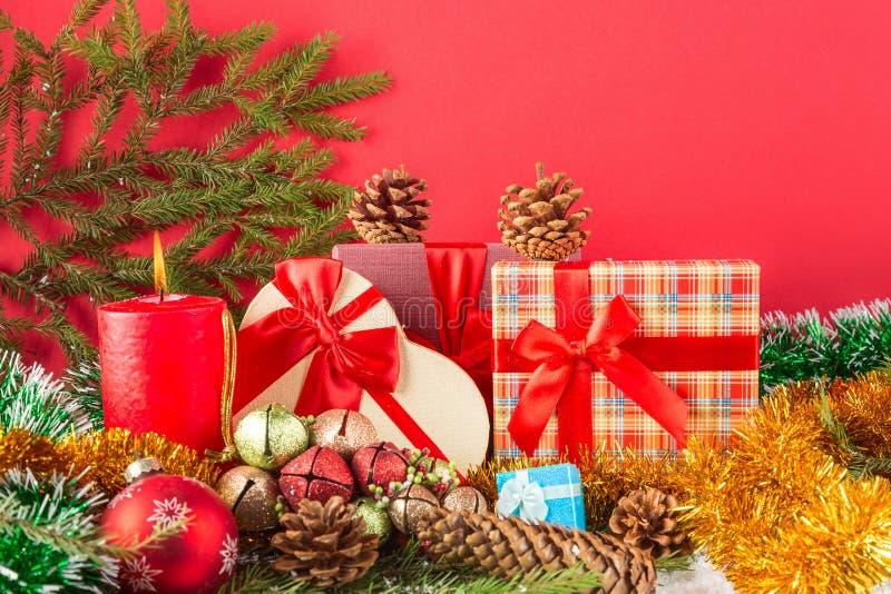 Scheda anno di nuovo o di natale La candela bruciante, i coni, i giftboxes, le palle con lamé e l'albero di Natale si ramificano  fotografie stock