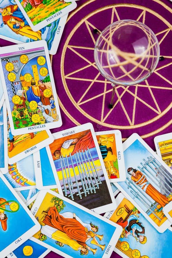 Schede di Tarot con una sfera magica su una tabella viola. fotografie stock libere da diritti