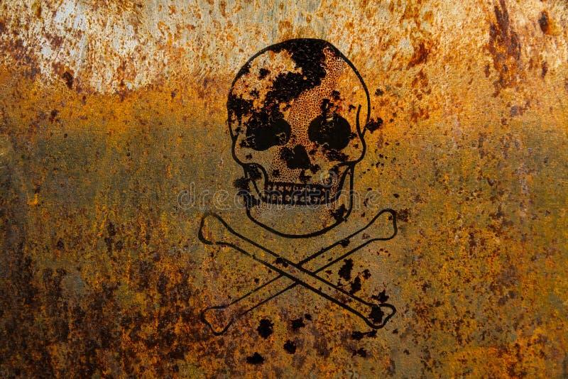 Schedel en gekruiste knekels symbolisch voor gevaar en levensgevaarlijk geschilderd over een roestige metaalplaat royalty-vrije stock foto