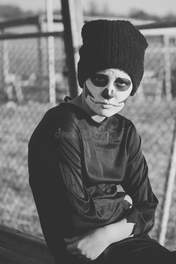 Schedel geschilderde jongen met een droevige uitdrukking stock fotografie