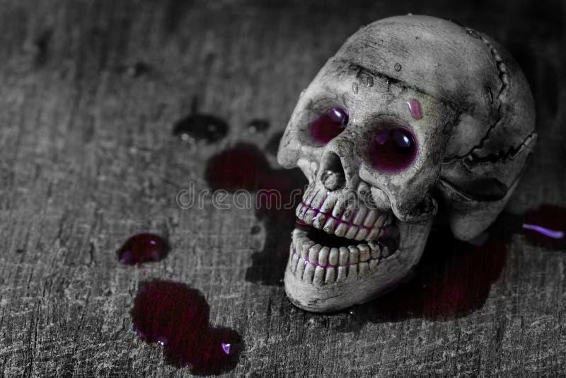 Schedel in het bloed op oude houten achtergrond stock afbeeldingen