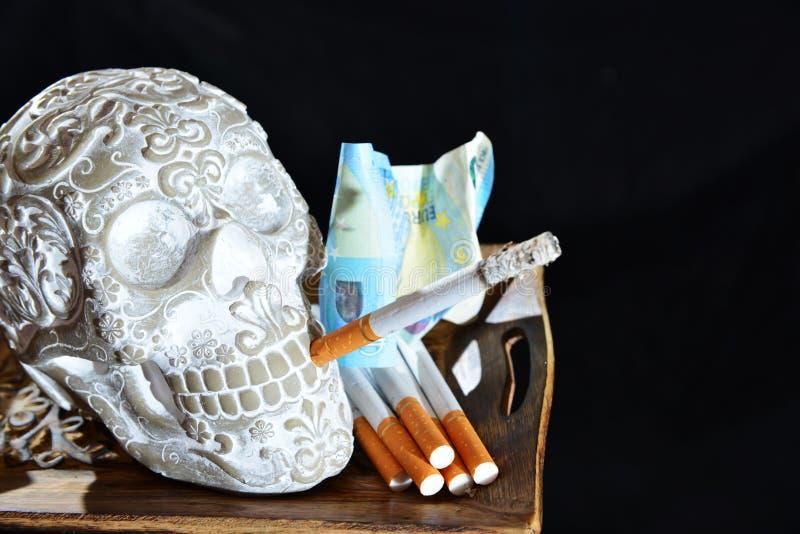 Schedel met het branden van sigaret stock foto's