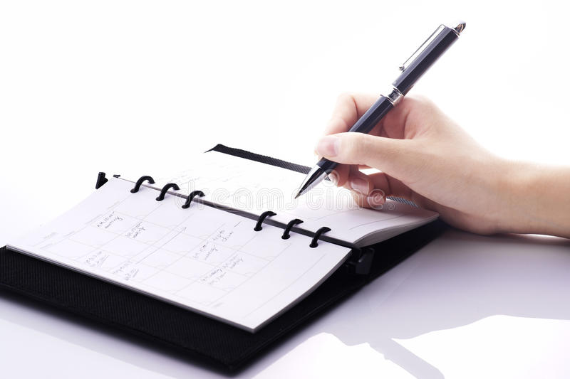 Schedule. Office woman is writing some words in her notebook royalty free stock images
