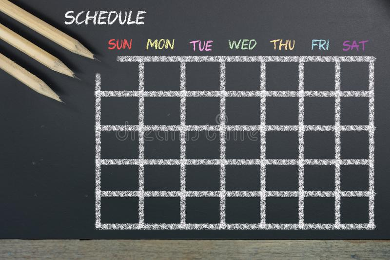 Schedule with grid time table on black chalkboard background stock photo