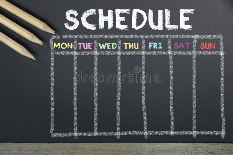 Schedule with grid time table on black chalkboard background royalty free stock photo