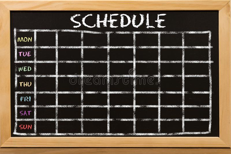 Schedule with grid time table on black chalkboard stock photo