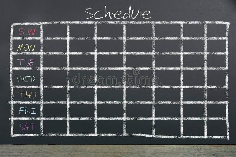 Schedule with grid time table on black chalkboard background stock image