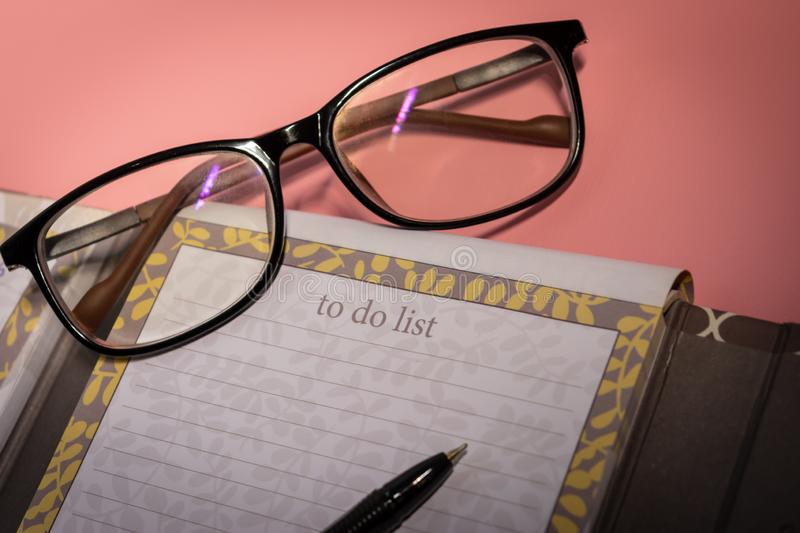 Schedule. Plan book with glasses and ballpoint pen pink background royalty free stock images