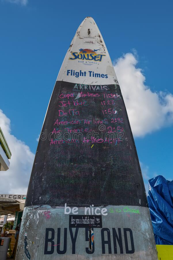 Schedule of plane arrival on Maho beach Princess Juliana International Airport, St. Martin. Simpson bay, Saint Maarten - December 17, 2018: Sunset Bar at Maho royalty free stock images