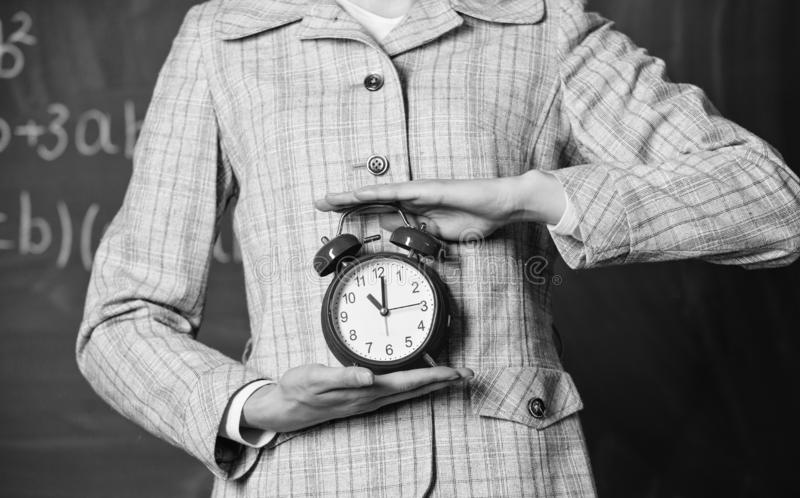 Schedule and regime. Alarm clock in female hands close up. Teachers attributes. Alarm clock in hands of teacher or royalty free stock photo