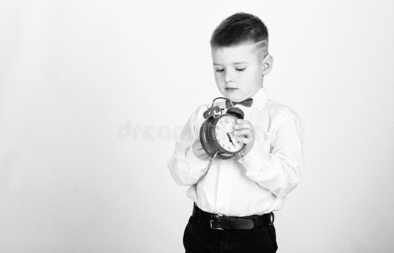Schedule and timing. Morning routine. Schoolboy with alarm clock. Kid adorable boy white shirt red bow tie. Develop self. Discipline. Set up alarm clock. Child royalty free stock photos