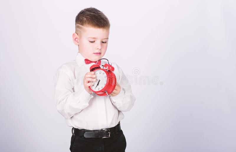 Schedule and timing. Morning routine. Schoolboy with alarm clock. Kid adorable boy white shirt red bow tie. Develop self. Discipline. Set up alarm clock. Child royalty free stock photo
