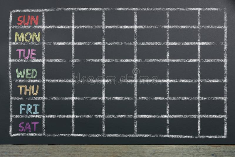Schedule of the week with grid on black chalkboard background royalty free stock photography