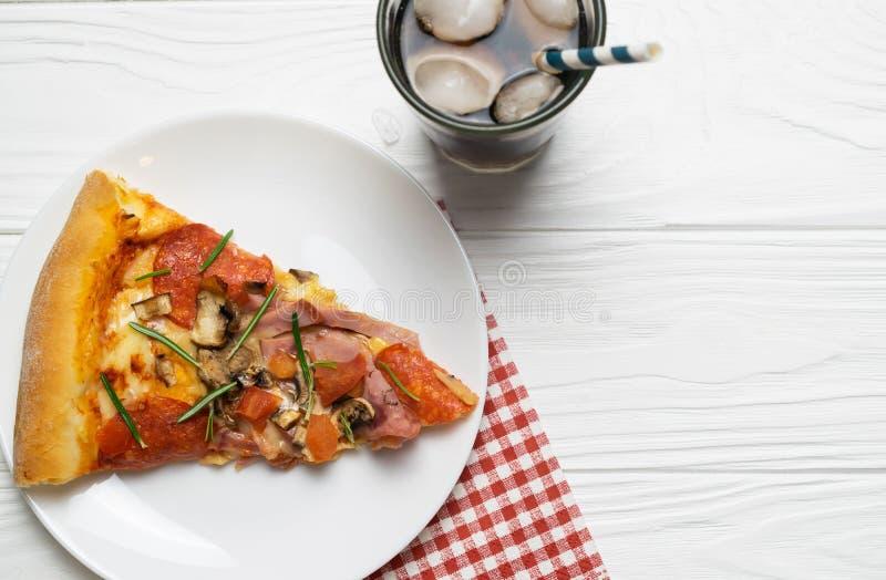 Scheibe der geschmackvollen Pizza mit Pepperoni-, Tomaten-, Käse- und Sodaeisgetränk lizenzfreie stockbilder