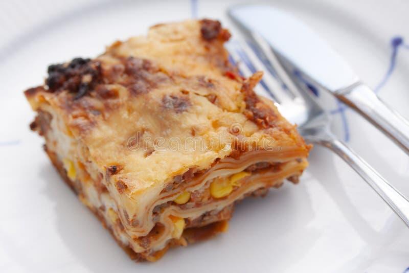 Scheibe der Lasagne auf einer Platte mit Gabel und Messer Abschluss oben stockbilder