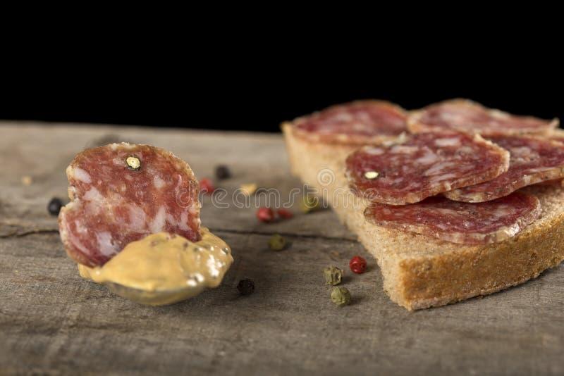 Scheibe der Salami in der Senfsoße lizenzfreies stockfoto