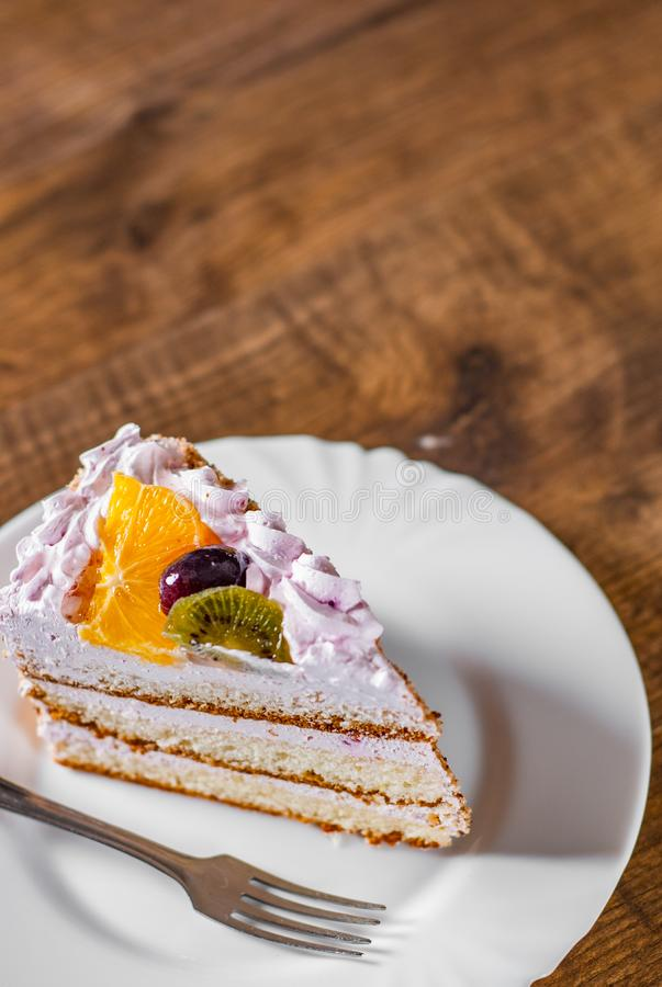 Scheibe des überlagerten Geburtstagskuchens mit Sahne mit Frucht in einer Platte auf hölzernem lizenzfreie stockfotografie