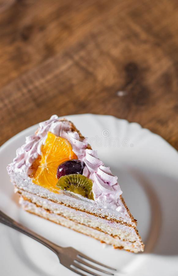 Scheibe des überlagerten Geburtstagskuchens mit Sahne mit Frucht in einer Platte auf hölzernem stockfotos
