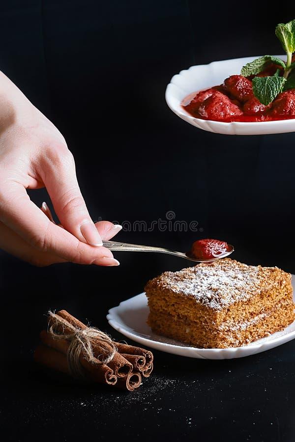 Scheibe des gegossenen Honigkuchens, Koch verziert mit Erdbeeren, Minze, Zimtstangen, Erdbeermarmelade, Abschluss oben, Platz für stockbild