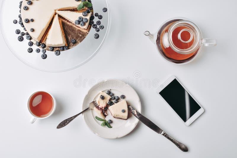 Scheibe des Käsekuchens mit Blaubeeren und Tee lizenzfreies stockbild