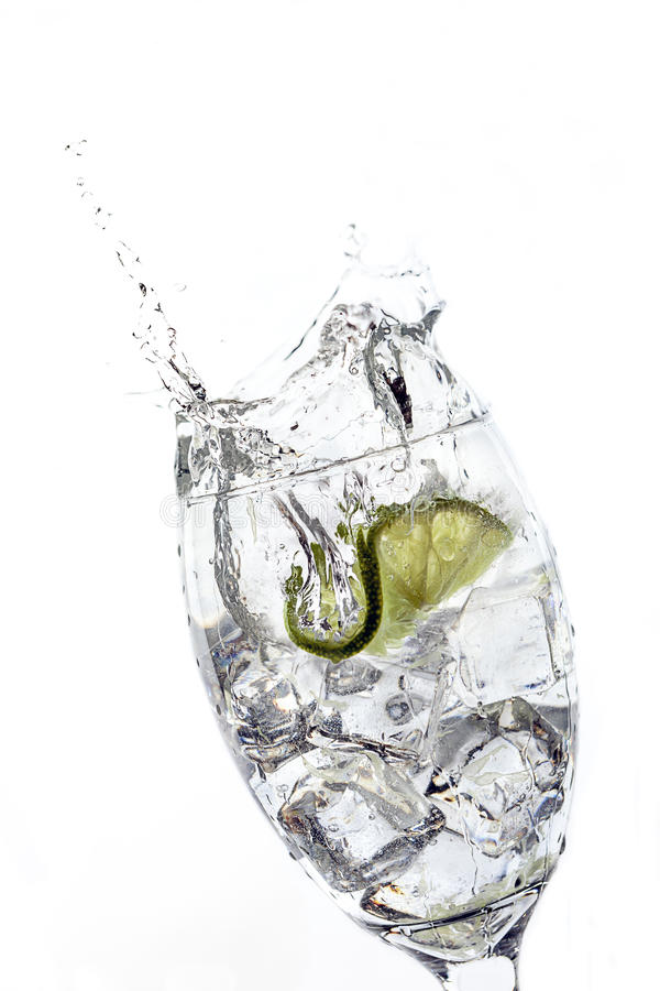 Scheibe des Kalkes fiel in Glas Wasser lizenzfreie stockfotografie
