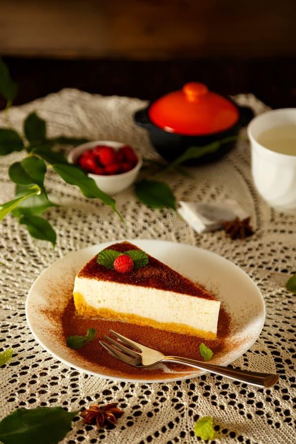 Scheibe des klassischen Käsekuchens oder des New- Yorkkäsekuchens mit einem Schokoladen- und Kakaopulver lizenzfreie stockfotografie