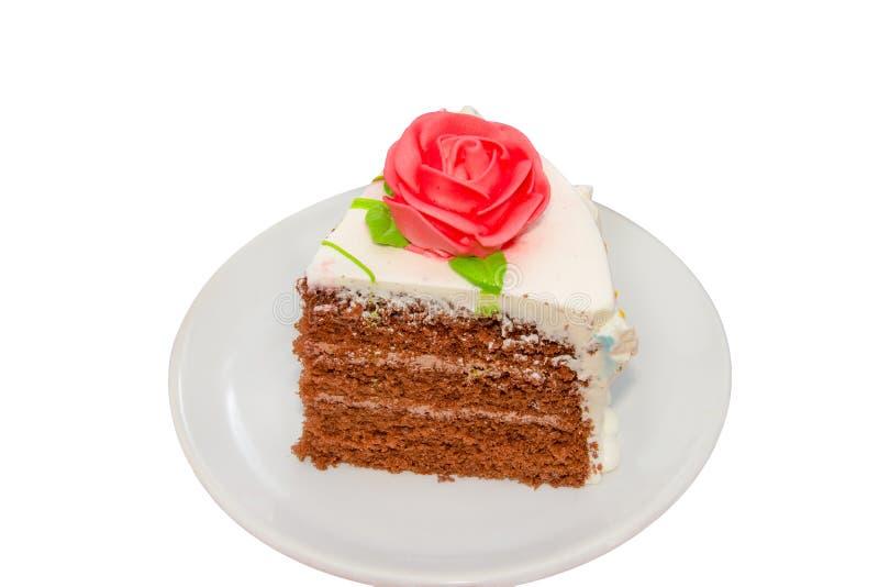 Scheibe des Schokoladencremekuchens mit der Rose lokalisiert auf Weiß lizenzfreies stockbild