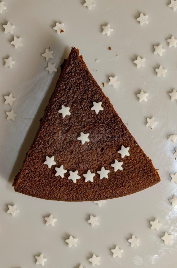 Scheibe des Schokoladenkuchens mit den Zuckersternen, die ein lächelndes Gesicht bilden stockfoto