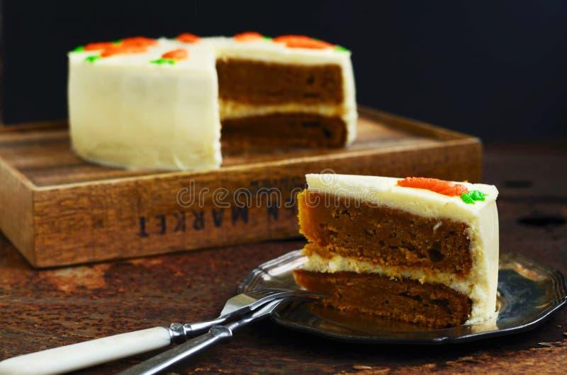 Scheibe des selbst gemachten Karottenkuchens mit Kopienraum auf dunklem Hintergrund lizenzfreies stockbild