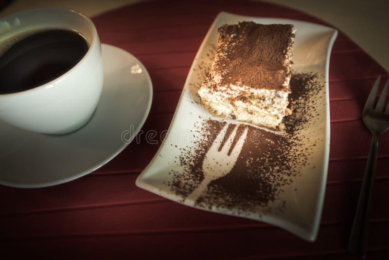 Scheibe des Tiramisu-Kuchens und der Schale schwarzen Kaffees stockbilder