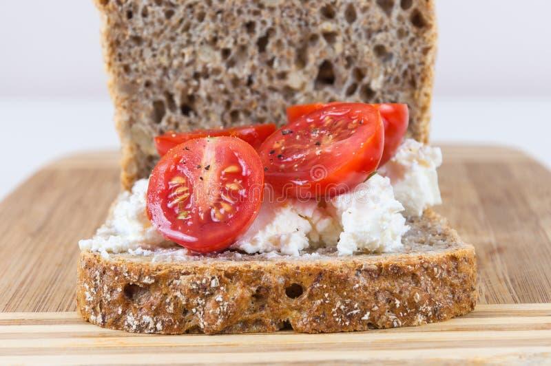 Scheibe des Vollkornbrotes mit Hüttenkäse und Kirschtomaten lizenzfreies stockfoto