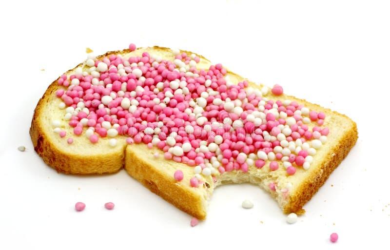 Scheibe des weißen Brotes und der kleinen farbigen Kugeln lizenzfreie stockfotos