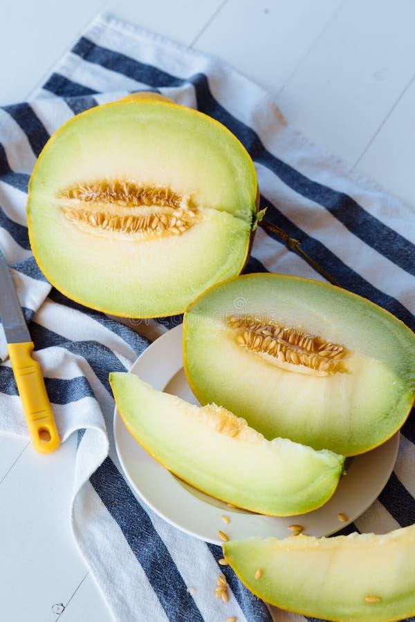 Scheiben der frischen Honigmelone auf einem weißen Holztisch lizenzfreies stockfoto